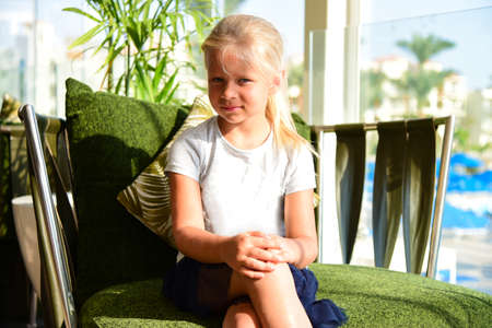A young girl in a dress sits on an easy chair in a sunny hotel.