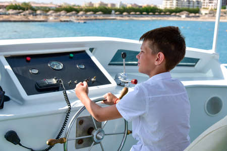 Teen at the helm controls a yacht at sea. Standard-Bild
