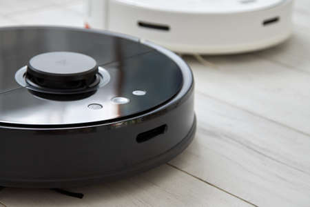 Black and white robot vacuum cleaners in automatically clean the floor. Black or white which one to choose?