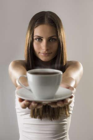 美しい少女は、コーヒーのカップを与える