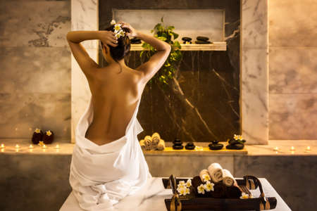 Beautiful girl in hammam. Tray with towels and flowers. Banque d'images