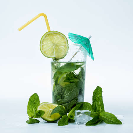 Fresh mohito cocktail with umbrella and drinking straw.