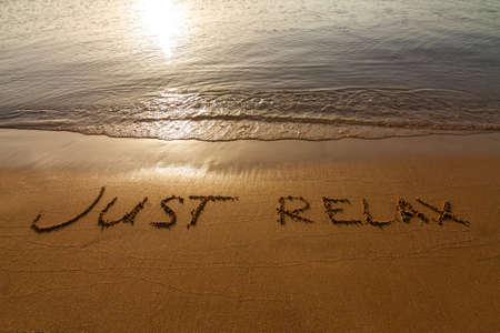 海の端の近くの砂の碑文: Just relax