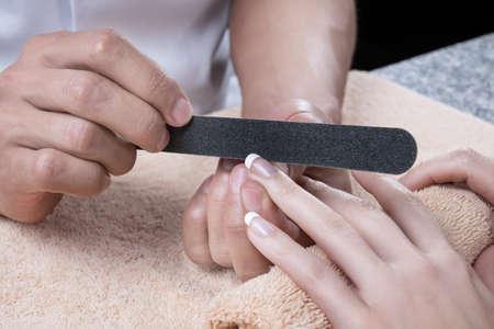 ネイルサロンでの女性は、美容師でマニキュアを受けています。爪やすりで爪の処理