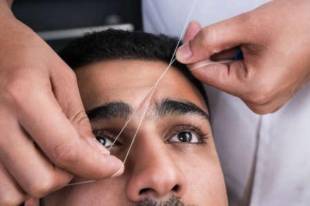 depilacion: La eliminación del vello facial cejas enhebrado procedimiento en salón de belleza Foto de archivo