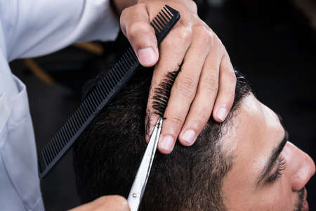 Professional hairdresser is cutting mens hair in beauty salon.