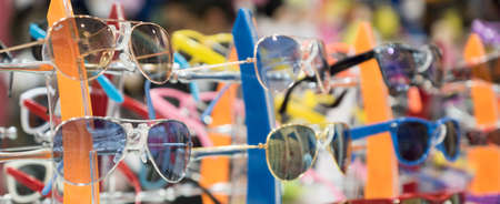The stand with childrens sunglasses in the kids shop Standard-Bild
