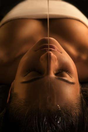 warm: The girl has Shirodhara treatment - indian oil massage. Stock Photo