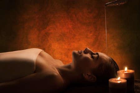masajes relajacion: La chica tiene el tratamiento Shirodhara - aceite de masaje indio.
