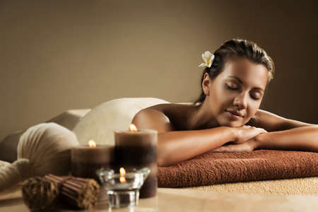 The girl relaxes in the spa salon. Beautiful setup with candles and herbal balls on the foreground.