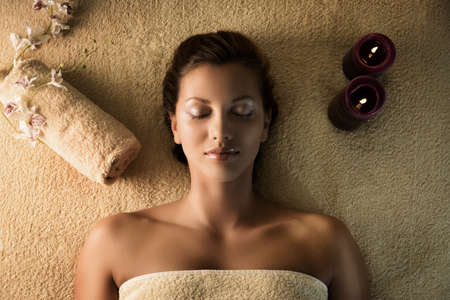 The young beautiful  girl relaxes in the spa.  Towel and candle setup.
