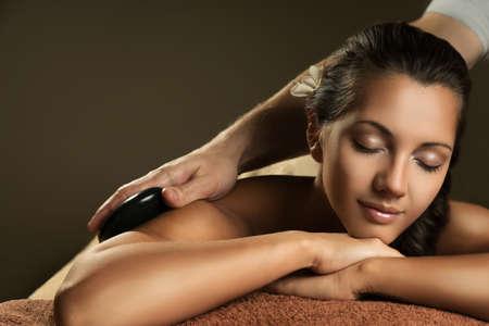 massages: Beautiful girl has hot stone massage. Spa treatment. Stock Photo
