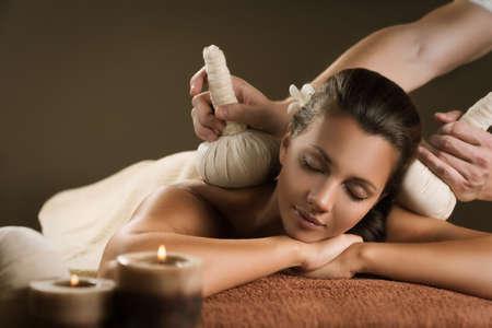 Massage mit Kräuterstempeln. Luxus-Spa-Behandlung