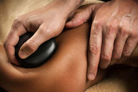 Massage mit heißen Basaltsteinen. Nahansicht. Spa-Behandlung. Standard-Bild