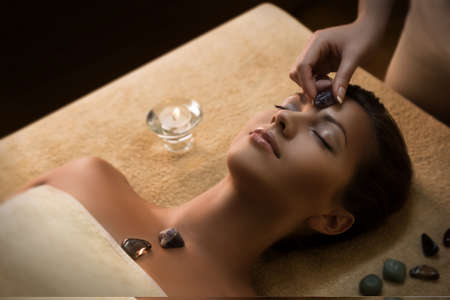people   lifestyle: Massage with special chakra-stones. Luxury addition to the traditional hot stone therapy. Stock Photo