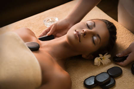 people   lifestyle: Massage with hot basalt stones. Beautiful deep charming light.