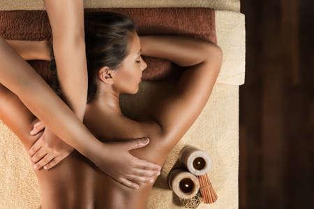 Das schöne Mädchen hat eine entspannende Massage. Spa-Behandlung. Candle-Setup