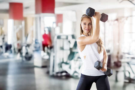 Young beautiful girl makes exercises with weight in gym. Blurred background