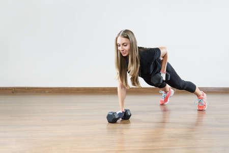 若い体育の授業で重量と女性が練習に合います。テキストを配置するためのスペース。