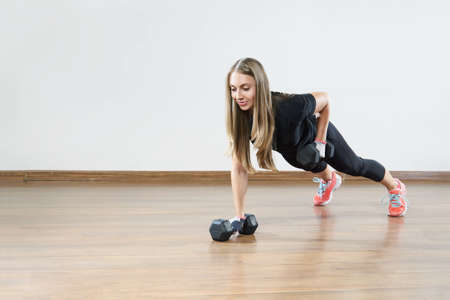 Young fit woman makes exercises with weight in gym class. Space for placing text .