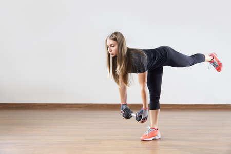 若い女性作品を体育の授業で重量合います。上げ足と運動します。テキストを配置するためのスペース。 写真素材