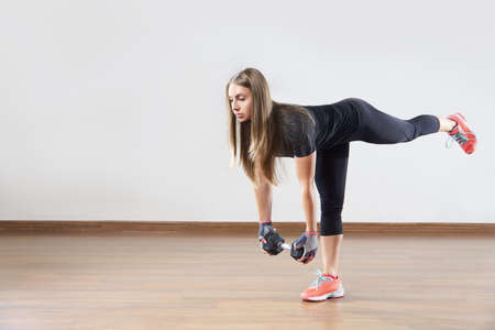 activewear: Young fit woman works out with weight in gym class. Exercise with the raised leg. Space for placing text . Stock Photo