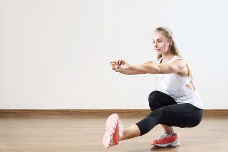 Young fit woman works out in the fitness class. Squats on one leg. Space for placing text. Stock Photo