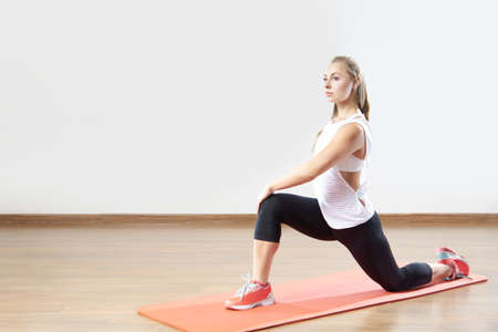 Young fit woman works out in the fitness class. Space for placing text.