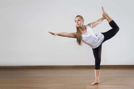 Young fit woman works out in the fitness class. Yoga asana. Space for placing text.
