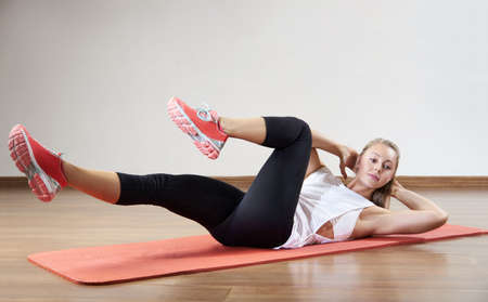 Young fit woman works out in the fitness class. Exercises for the abs. Space for placing text.