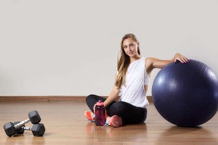 フィット若い女性リラックス体操ボール近く訓練の後。幸福、健康とフィットネスの概念。