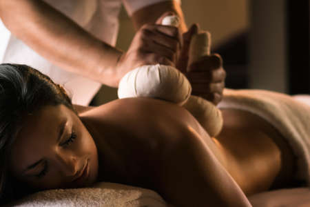 esthetician: Massage with herbal balls. Luxury spa treatment