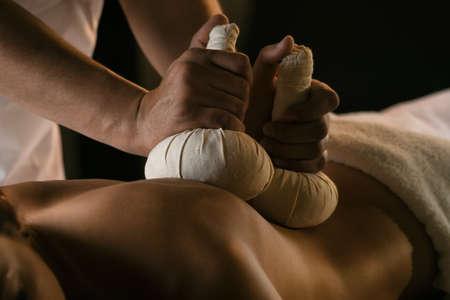 Eine junge Frau genießt eine Massage mit Kräuterbällen. Luxus-Spa-Behandlung