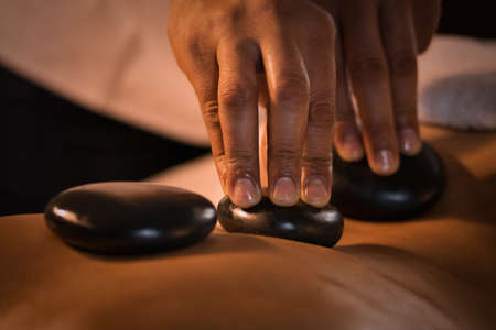 Closeup of massage with hot stones. Spa treatment.