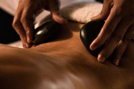 Nahaufnahme der Massage mit heißen Steinen. Spa-Behandlung.