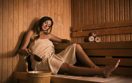 The girl relaxes in a sauna and plays with water.