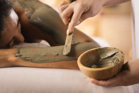 mud girl: Closeup of applying mud mask with hands of professional therapist. Stock Photo