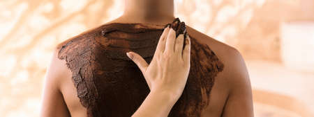 Applying a chocolate mask to the body. Luxury SPA treatment.