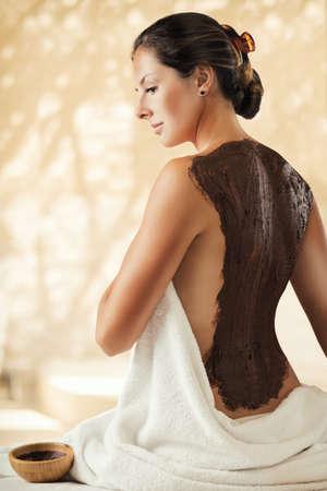 The girl enjoys chocolate body mask in a spa salon. Luxury treatment