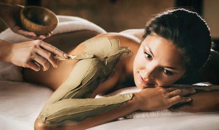 Das Mädchen genießt Schlamm Körper Maske in einem Spa-Salon. Fokus auf die Hand mit dem Stock. Luxusbehandlung