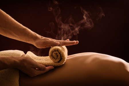 Ein professioneller Therapeut wendet ein heißes Handtuch auf der Rückseite eines Mannes an. Heißtuch komprimieren Spa-Behandlung