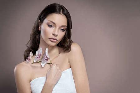 Junge und gesunde Frau mit hellem Make-up hält die Orchideenblume. Beige Hintergrund.