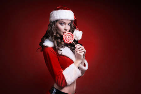 Beautiful young Santa girl with candy on red background. Standard-Bild