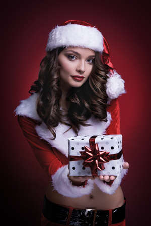 Beautiful young Santa girl with gift on red background. Standard-Bild