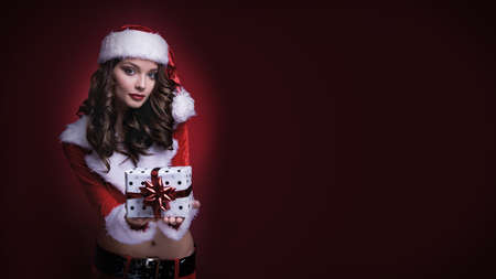 Beautiful young Santa girl with gift on red background. Brunette model giving box with ribbon. Copy space. Standard-Bild