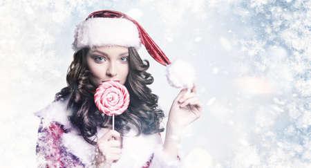 雪の冬の背景にキャンディを持つ若い美しい女の子。凍結ガラスの後ろのブルネットモデル。クリスマスと年末年始のコンセプト。