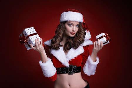 赤い背景に贈り物を持つ美しい若いサンタの女の子。2つの箱を保持するブルネットモデル。 写真素材