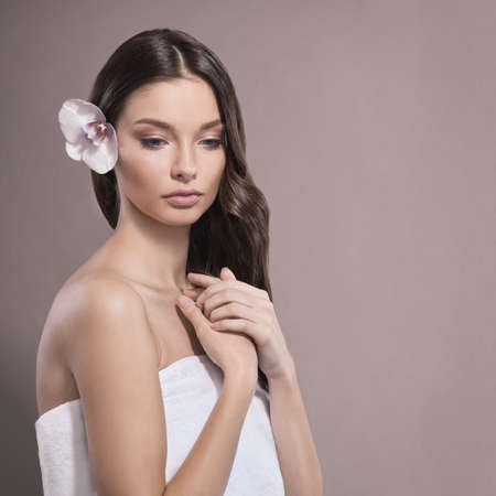 Young and healthy woman with light make-up and Orchid flower. Beige background. SPA and skin care concept. Copy space. Standard-Bild
