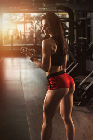 Young fit athletic girl having workout in gym. Brunette beautiful healthy female indoor training. Standard-Bild - 131685205