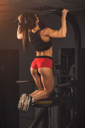 Young fit athletic girl having workout in gym. Brunette beautiful healthy female indoor training.